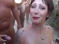 A beautiful French Beach slut sucks one dick after the other and gets showered with cum.