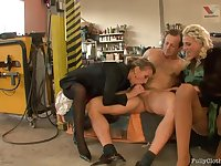 Blonde woman in a fur coat is having a threesome in the workshop and enjoying it
