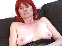 Red haired granny in erotic lingerie is having casual sex with a black guy, on the sofa